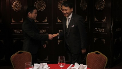 Businessmen meeting and shaking hands in Chinese restaurant