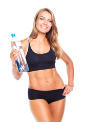 Young athletic girl with bottle of water on white