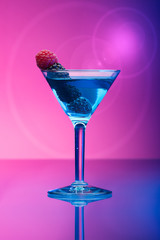 Colourful cocktail with berries, light effects background