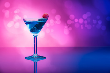 Colorful cocktails with berries, light effects background