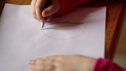 Little girl draws pencil on paper. close-up