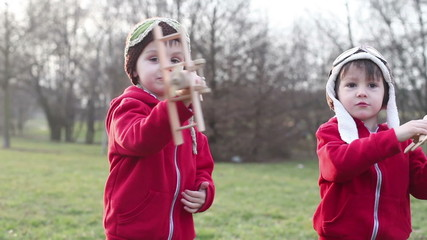 Happy kids playing with toy airplane, springtime