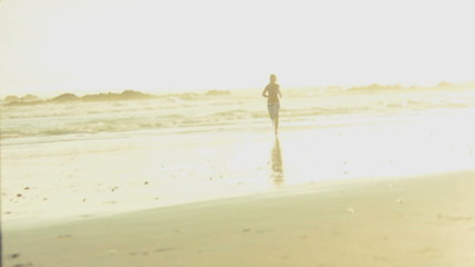 WS OF A YOUNG WOMAN RUNNING FROM THE SEA