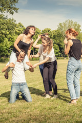Group of five teenagers joking at the park in summer