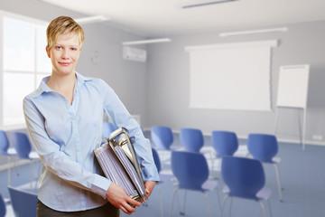 Frau mit Akten im Schulungsraum zur Weiterbildung