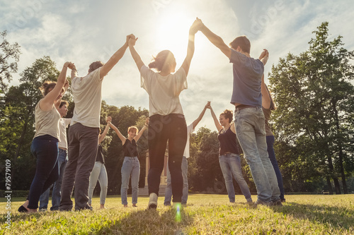 Group of ten friends at the park holding hands - 79579109
