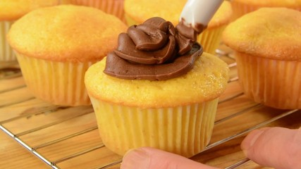 Putting frosting on freshly baked cupcakes