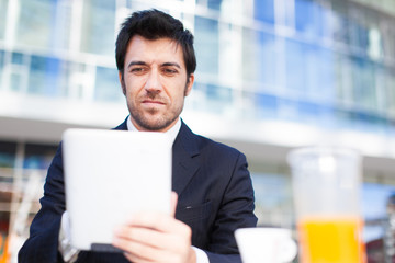 Businessman using his tablet while having breakfast