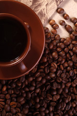 Cup of coffee on beans, view from above