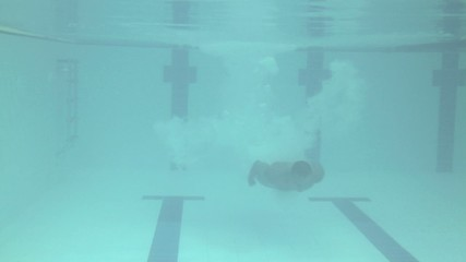 Male jumping into swimming pool in gym