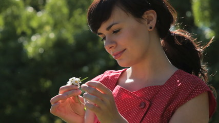 Female smelling daisy in park