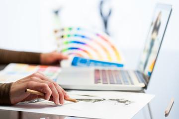 Designer hand making sketch with color chart.
