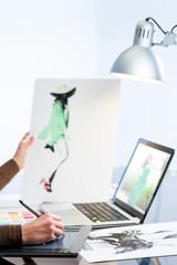 Female hand designing dress on computer.