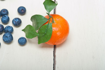 tangerine and blueberry on white table