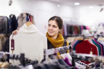 girl choosing  sweater at  shop