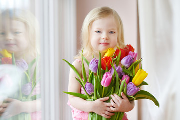 Adorable toddler girl holding tulips by the window