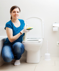 Smiling girl  cleaning  in bathroom at home