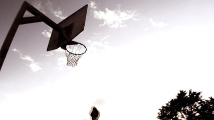 Basketball players dunking basketball in basket, London, UK