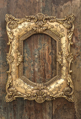 Vintage golden frame on wooden background. Grunge texture