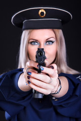 Woman in a marine uniform with a gun (focus is on the gun)