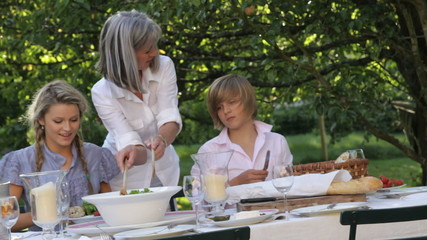 Mother serving daughter and son salad in garden