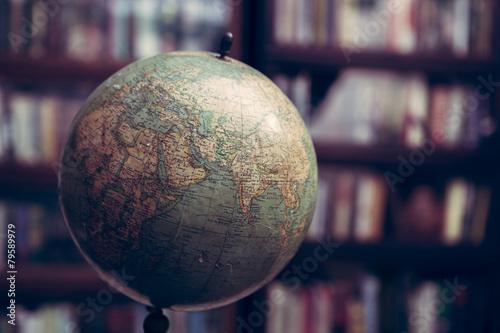 Leinwanddruck Bild Globe in a library