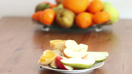 Plate with cut fruits and a bowl of fruits