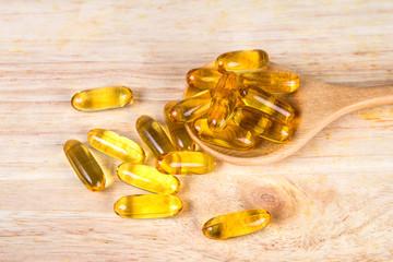 Closeup yellow soft gelatin supplement fish oil capsule on woode