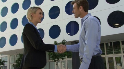 Male and female greeting with handshake