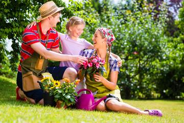 Familie gärtnert im Garten und hat Spaß