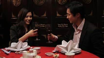 Couple toasting in Chinese restaurant