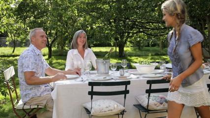 WS, Family in garden daughter serves salad