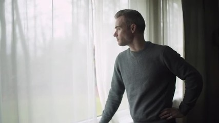 A depressed man stands at a window on a stormy cold day and looks out the window.