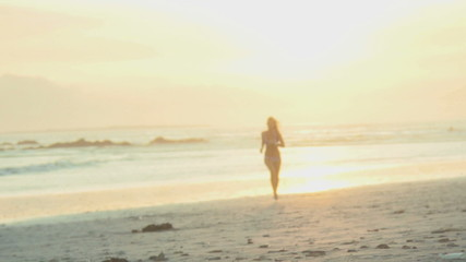 SLO MO WS OF A YOUNG WOMAN RUNNING ON A BEACH