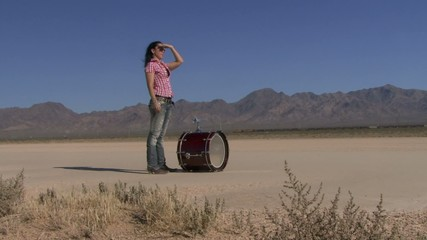 Female standing with a drum in desert