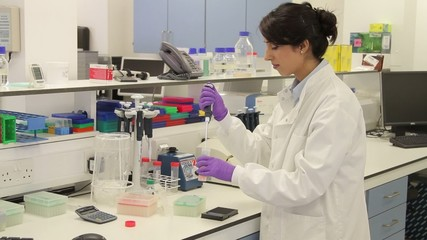 Scientist dropping liquid with pipet into vial in genetic laboratory