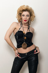 Sexy blond adult woman in black corset and leather trousers