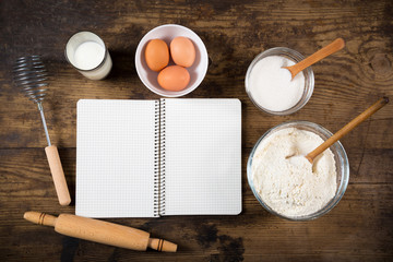 baking ingredients and cookbook on table