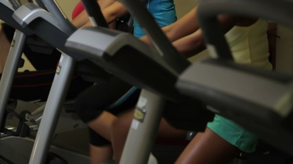 Females working out on bicycles in a gym