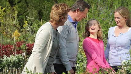 Grandparents, daughter and granddaughter looking at plants in garden centre
