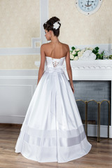 Young beautiful bride standing in luxurious wedding dress