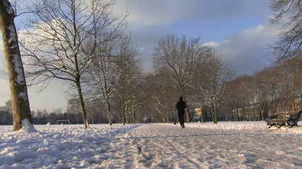 LS OF JOGGERS RUNNING IN THE SNOW IN VICTORIA PARK LONDON