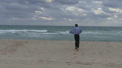 Male taking his suit off and running into an ocean