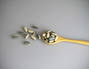 Herbal Supplement vitamin pills or tablets in wooden spoon