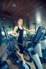 beautiful girl doing indoor biking in a fitness club