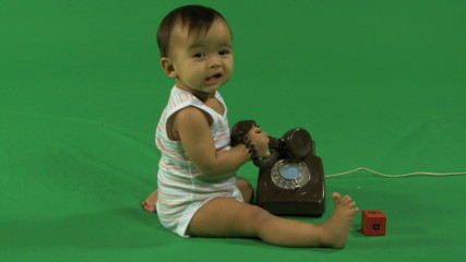 LS OF A BABY PLAYING WITH A TELEPHONE