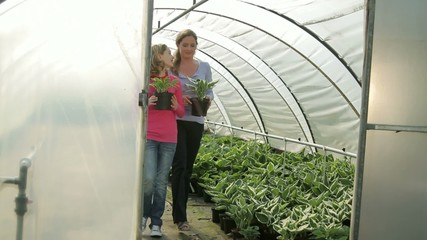 Mother and daughter (11) looking at plants in green house in garden centre