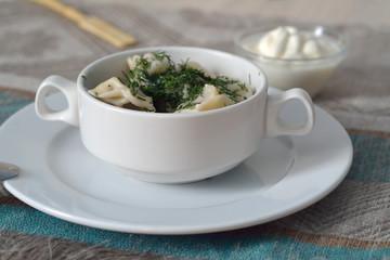 Pelmeni in a bowl with sour cream