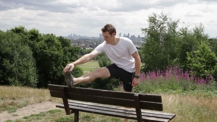 Male stretching on bench in park