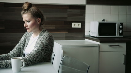 Young woman using computer in modern kitchen interior.